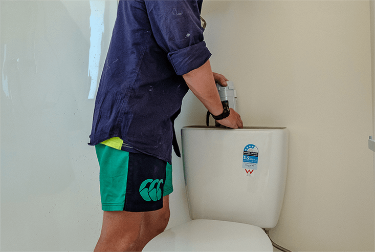 plumber installing new toilet in bathroom