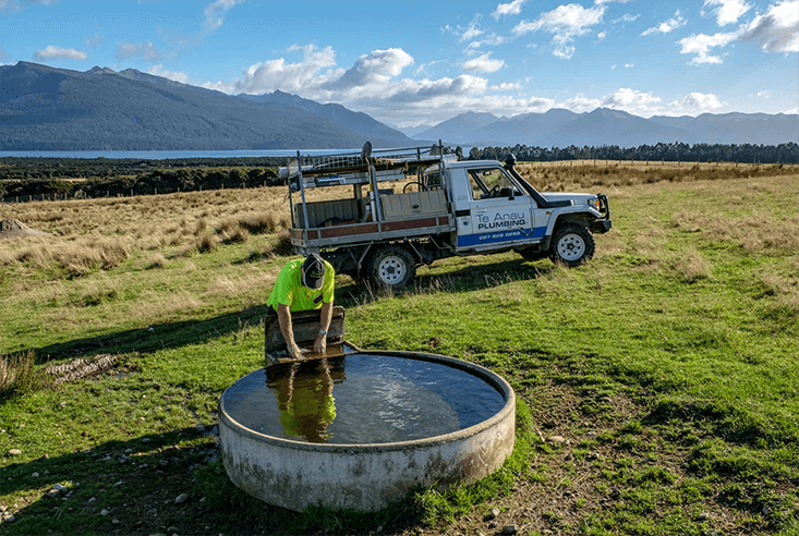 Two Te Anau Plumbers moving a large water tank into place for a rural water scheme.