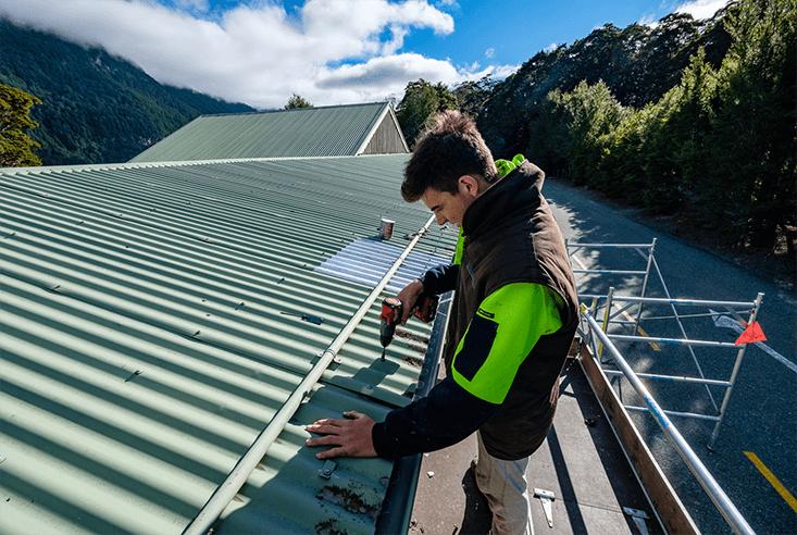 Te Anau plumber standing on scaffolding repairing a roof.