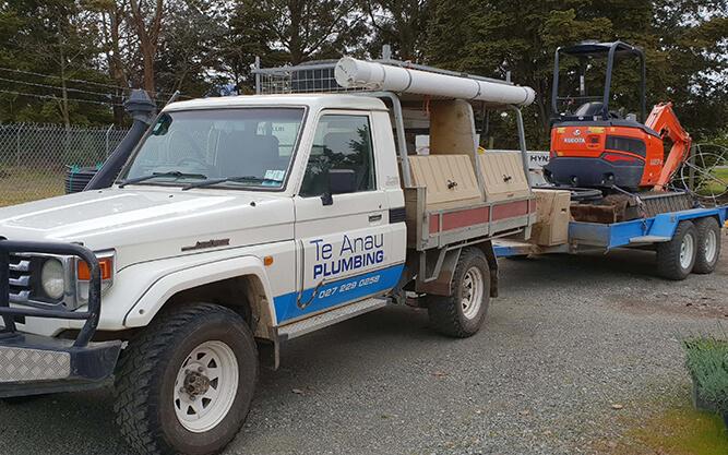 Te Anau Plumbing truck with digger on trailer